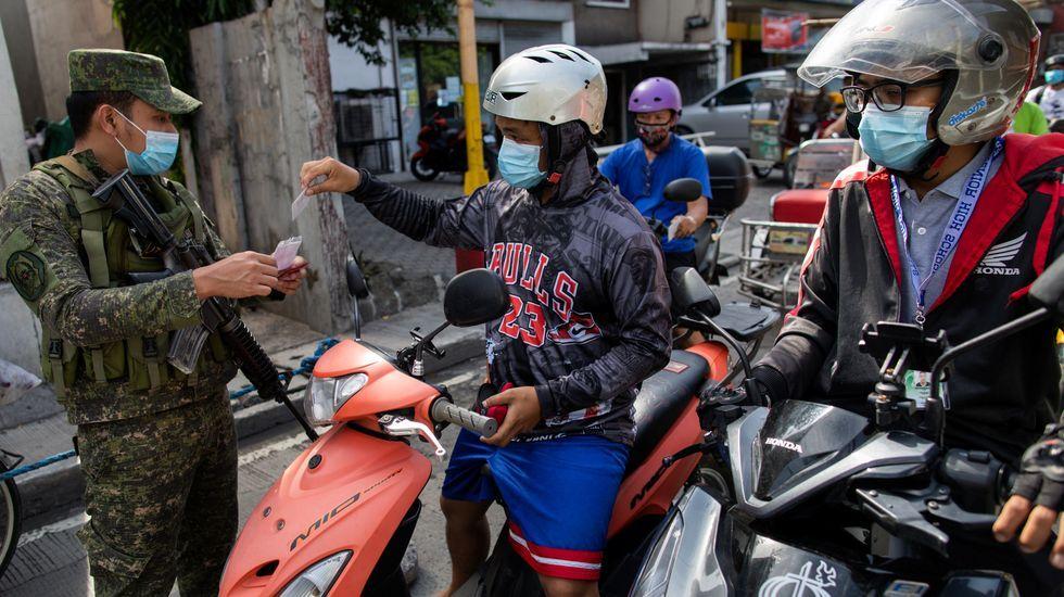 Un policia armado compueba un control de la cuarentena en Manila, Filipinas