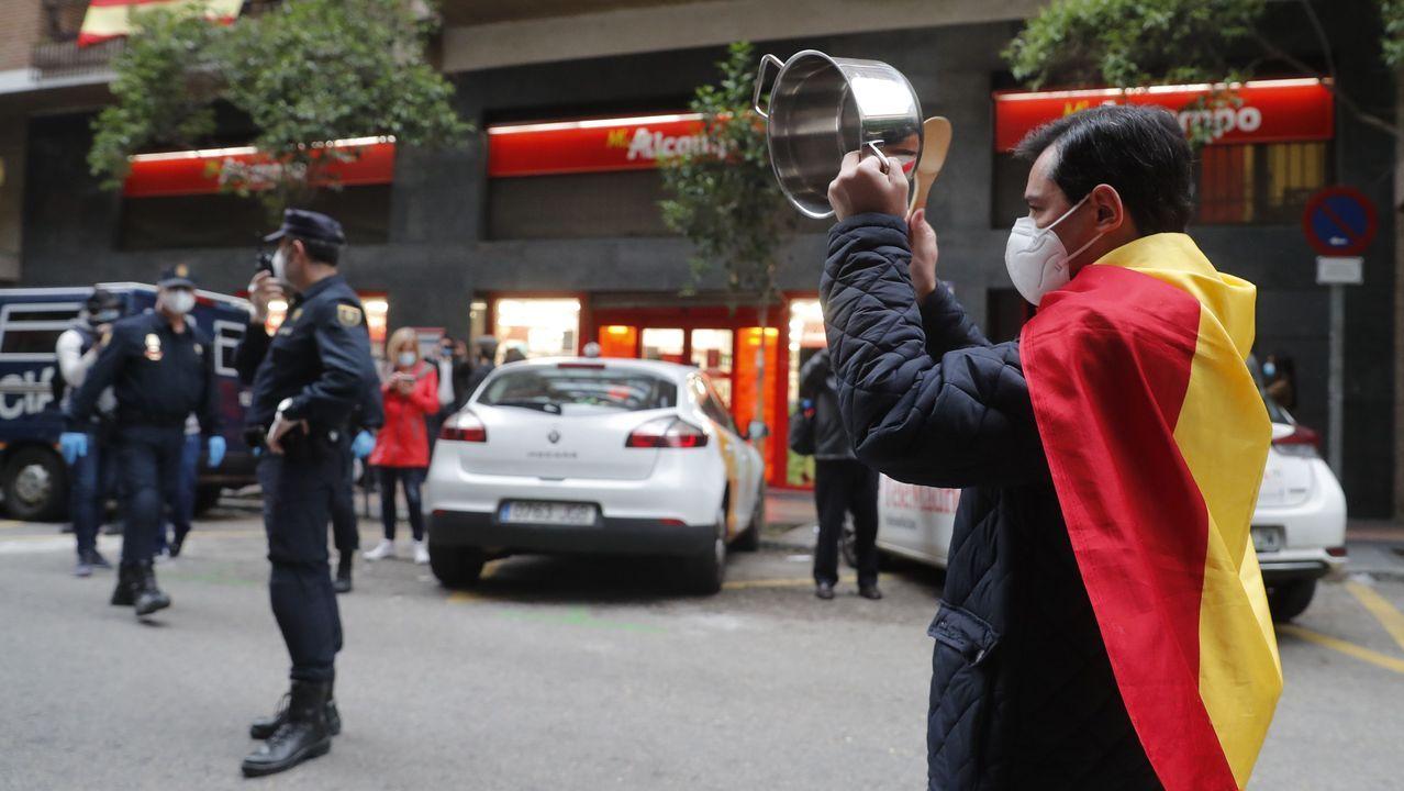 Cacerolada al grito de «Gobierno dimisión» en el centro de Madrid sin respetar la distancia de seguridad.Un agente conversa con una manifestante este lunes en el barrio de Salamanca