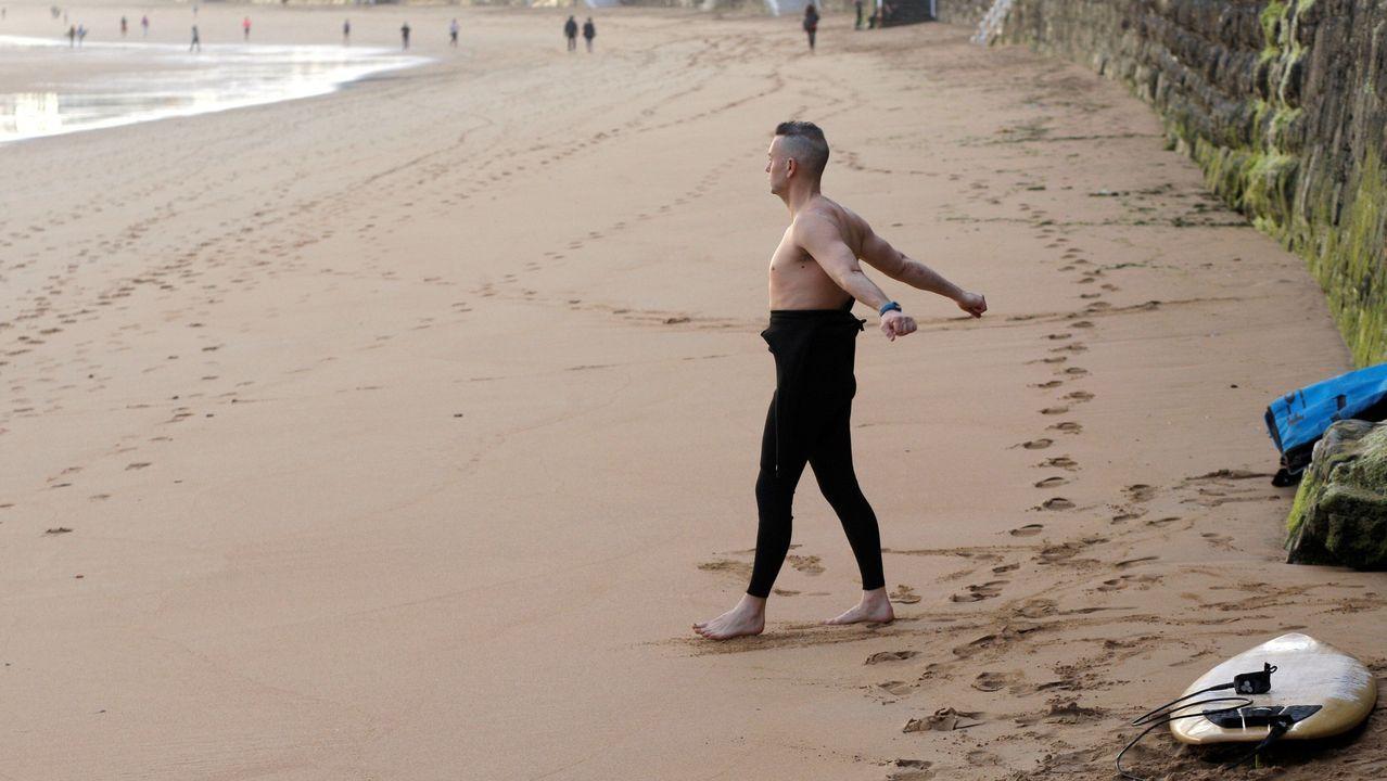 Un surfista realiza estiramientos antes de entrar al agua en la Playa de San Lorenzo de Gijón