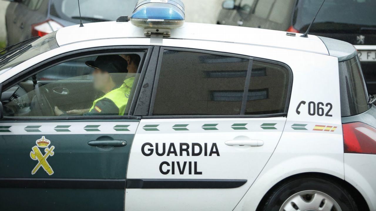 Un policía sale del Concello de Santiago con material requisado