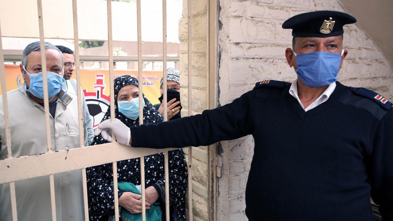 Un soldado egipcio organiza la cola de pensionistas que acuden a recoger su subsidio mensual en El Cairo