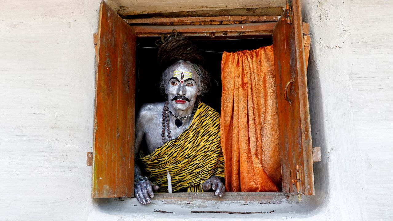 Un devoto vestido de dios Shiva observa por una ventana durante el festival anual en honor de la deidad hindú