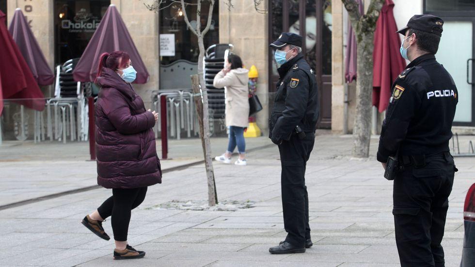 Dos policías vigilan en Monforte el cumplimiento de las restricciones contra el covid-19, junto a la terraza de un bar que da cafés para llevar