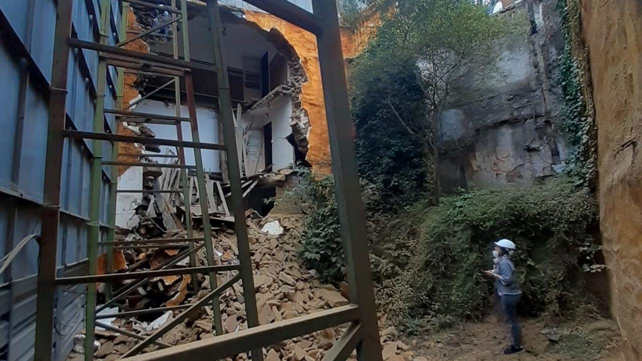 Un técnico revisa el estado del inmueble tras el derrumbre del muro