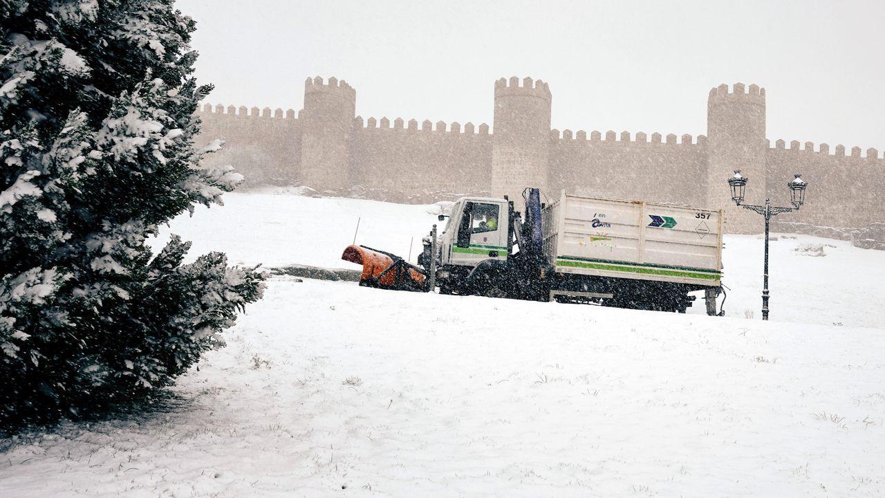 Una máquina quitanieves retira la nieve caída este lunes junto a la muralla de Ávila