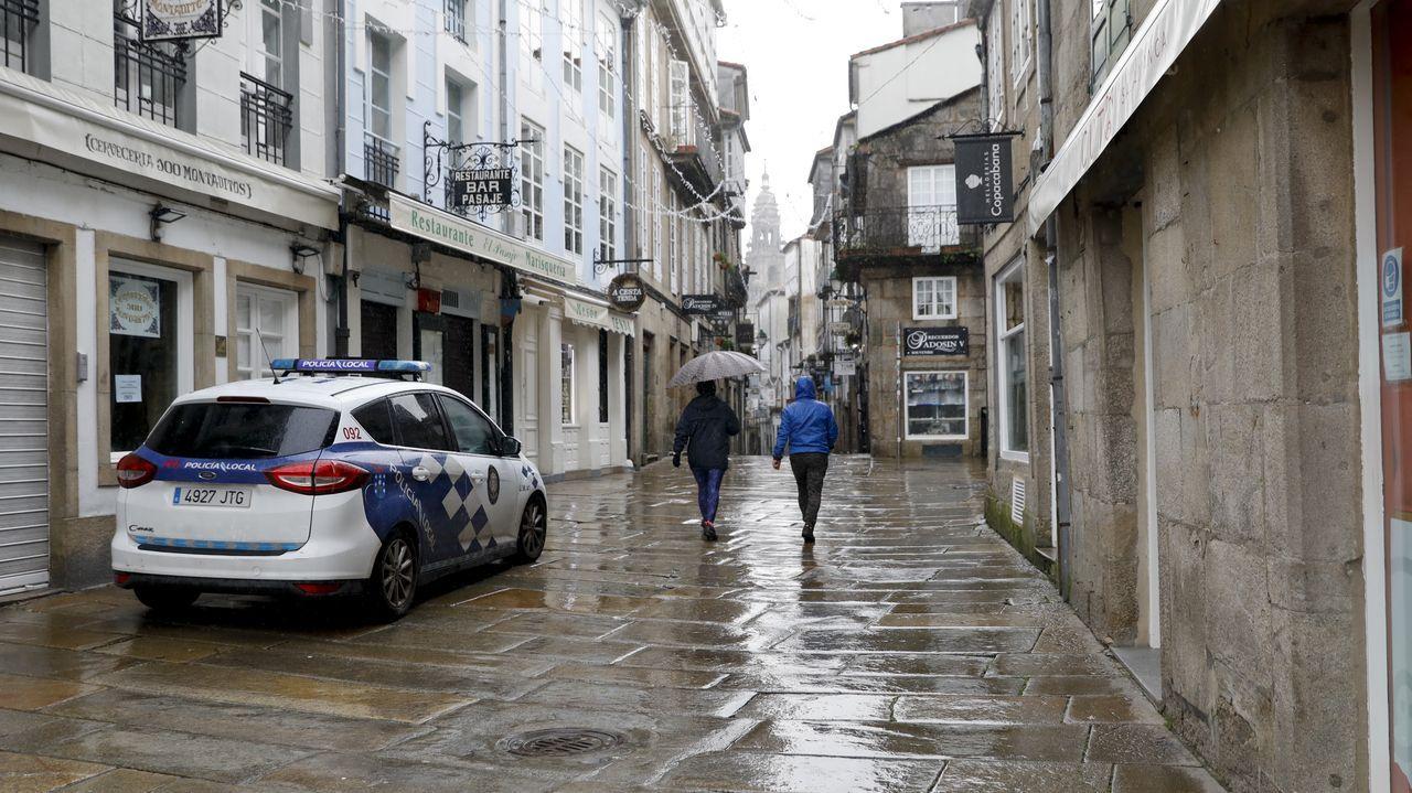 Calles vacías y negocios cerrados en el primer día de nuevas restricciones por la tercera ola de la pandemia.Una patrulla de la Policía Local de Santiago vigila el cumplimiento de la normativa covid en la zona monumental de la ciudad