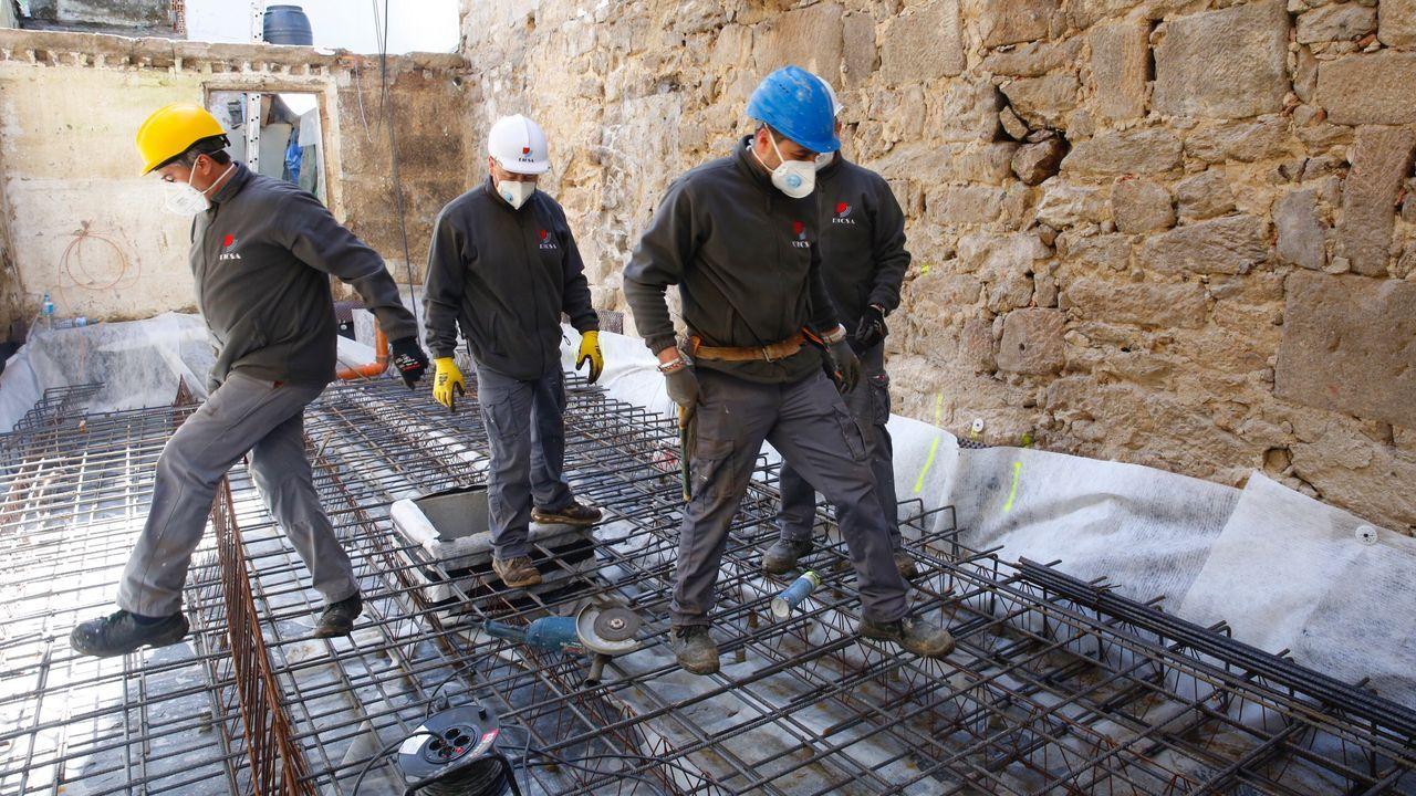 Obreros de la construcción trabajando en un edificio de la calle San Román de Pontevedra
