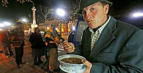 Felipe VI regresa a Portugal como rey.Un grupo de voluntarios reparte comida caliente entre ciudadanos con pocos recursos en las calles de Lisboa.