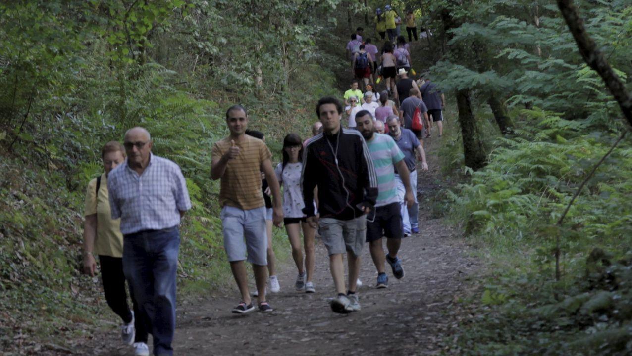Personas caminando por la senda que lleva a Os Caneiros en una de las jiras