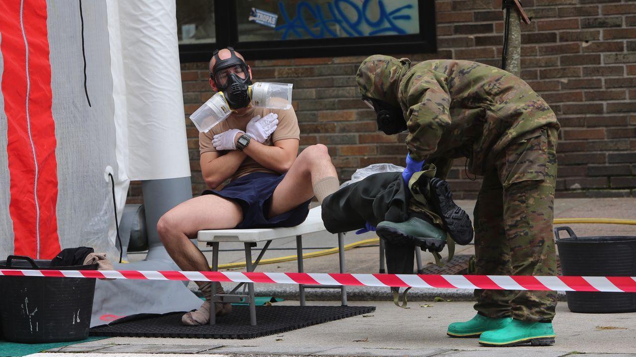 Un soldado con traje de protección ayuda a su compañero a retirarse el suyo adecuadamente