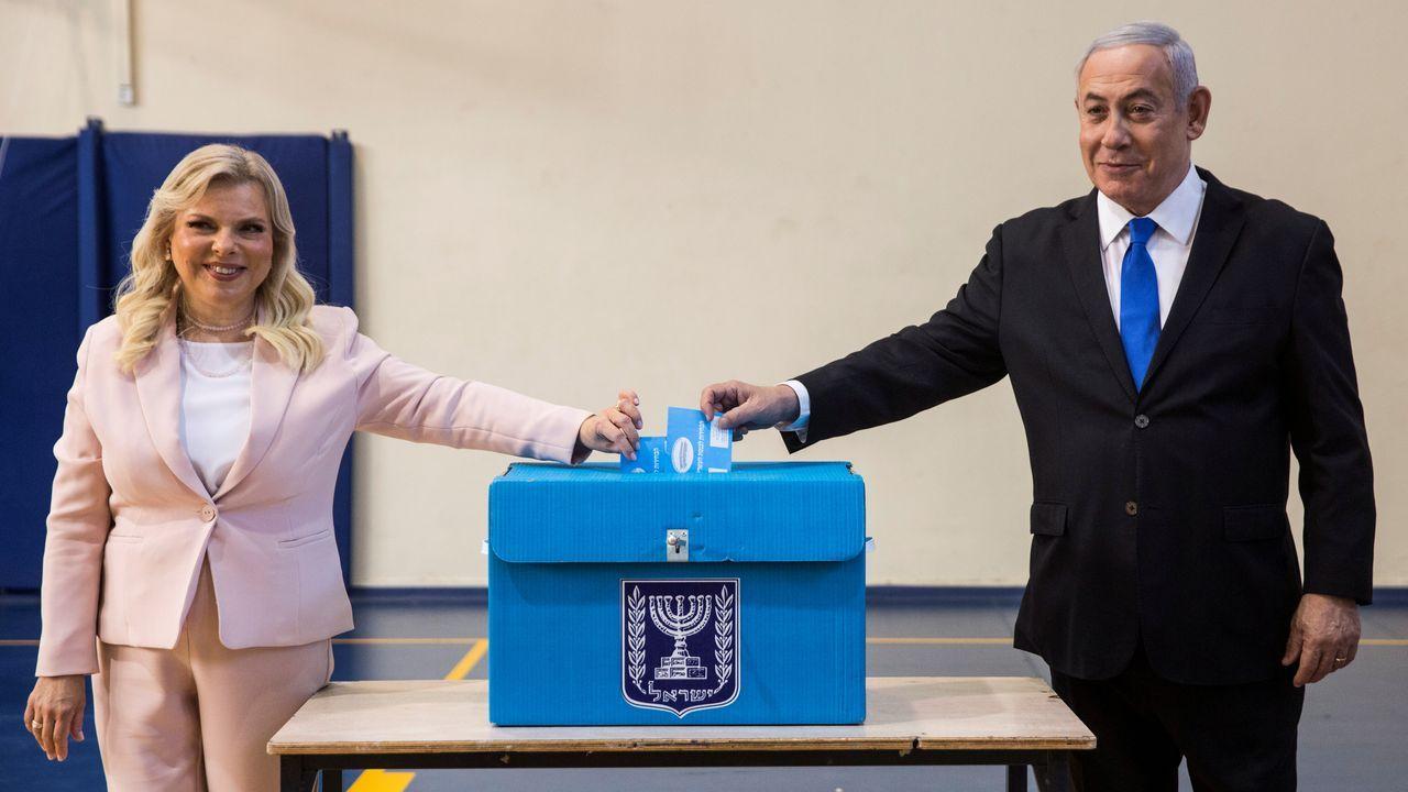 El primer ministro en funciones, Benjamin Netanyahu, deposita junto a su mujer el voto