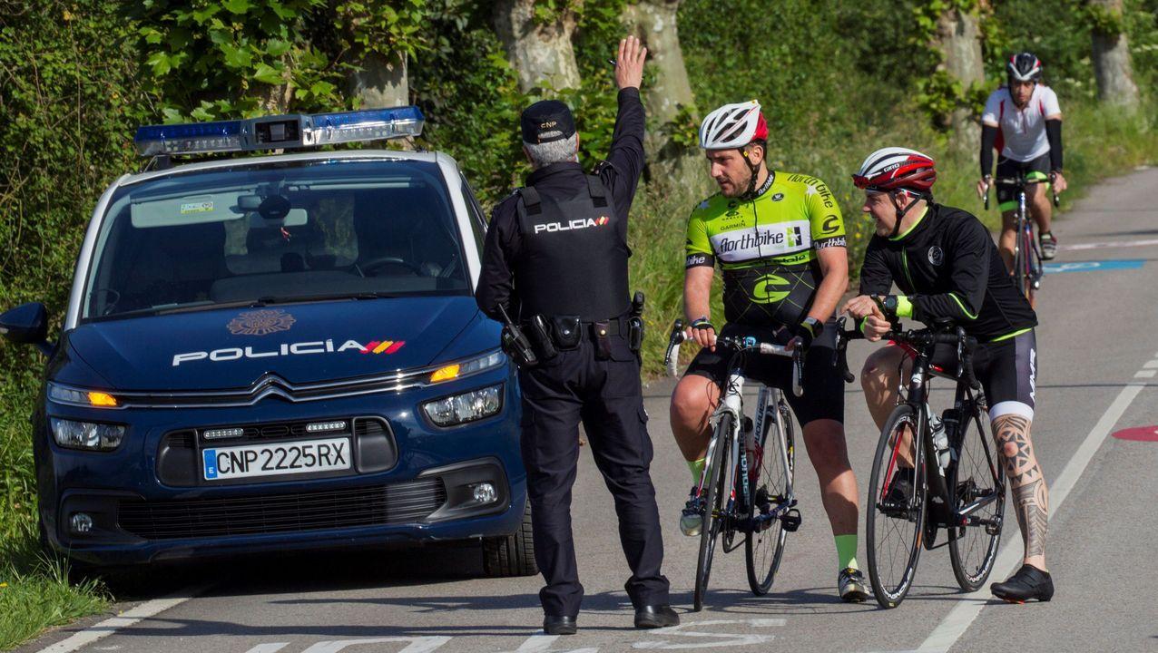 Un policía para a un grupo de ciclistas, en la falda del monte Naranco de Oviedo, en el segundo día que se permiten los paseos de adultos y el deporte individual al aire libre. EFE/Alberto Morante