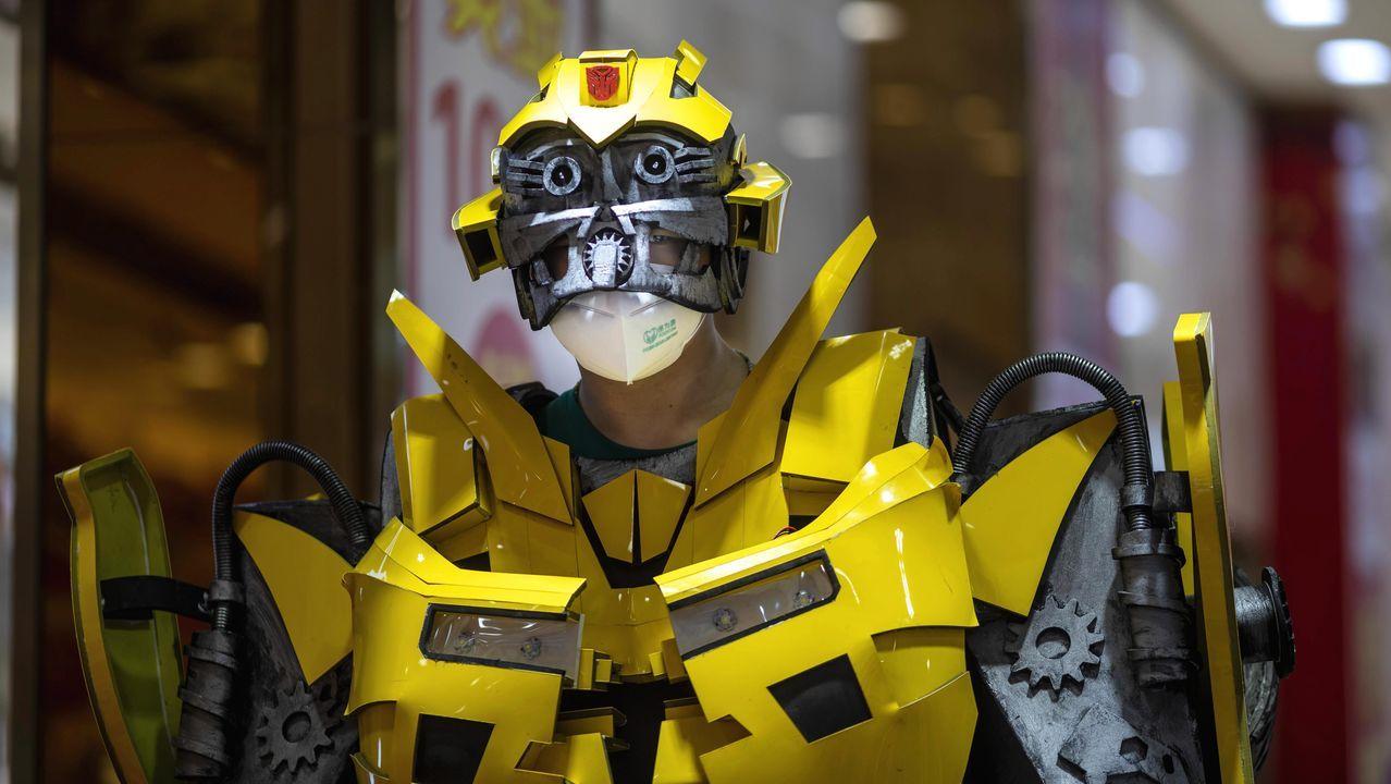 Un hombre con una máscara y vestido como un robot Transformer promociona una tienda de oro en Guangzhou