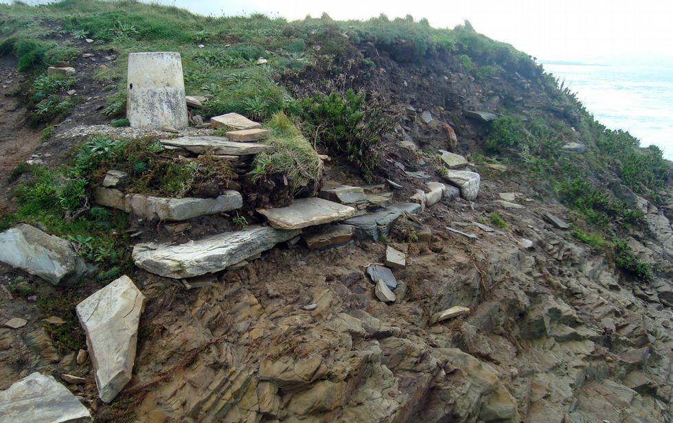 Ballena muerta en Redondela.El muro del castro de San Miguel, que está siendo destrozado por el embate de las olas.