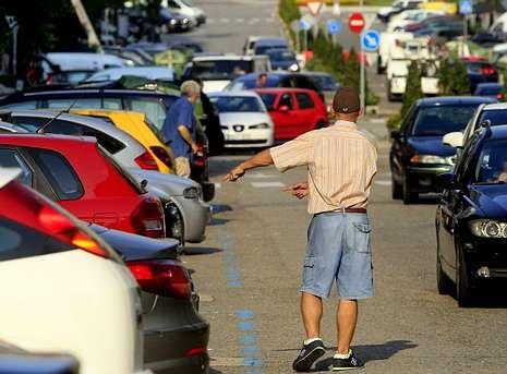 Un gorrilla busca propina como aparcacoches en Rosalía de Castro, en la tarde de ayer.