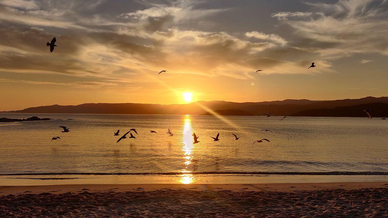 tiempo.Personas con mascarilla en la playa de Oza. Imagen de archivo
