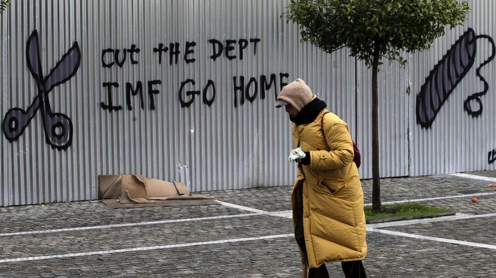 Una mujer pasa ante un grafiti en el que se lee «Rebaja la deuda. FMI vete a casa» en una valla de la Academia de las Ciencias de Atenas.