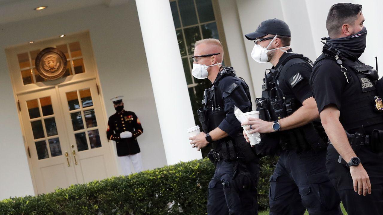 Un marine y miembros del servicio secreto vigilan la entrada al ala oeste de la Casa Blanca