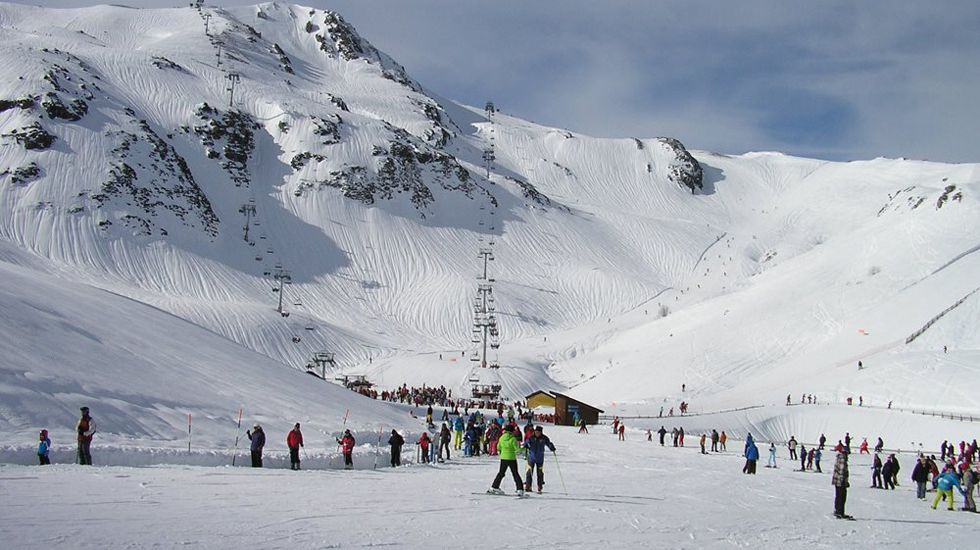 Los esquiadores disfrutan de la nieve con la estación de esquí de Valgrande-Pajares al fondo.Fuentes de Invierno