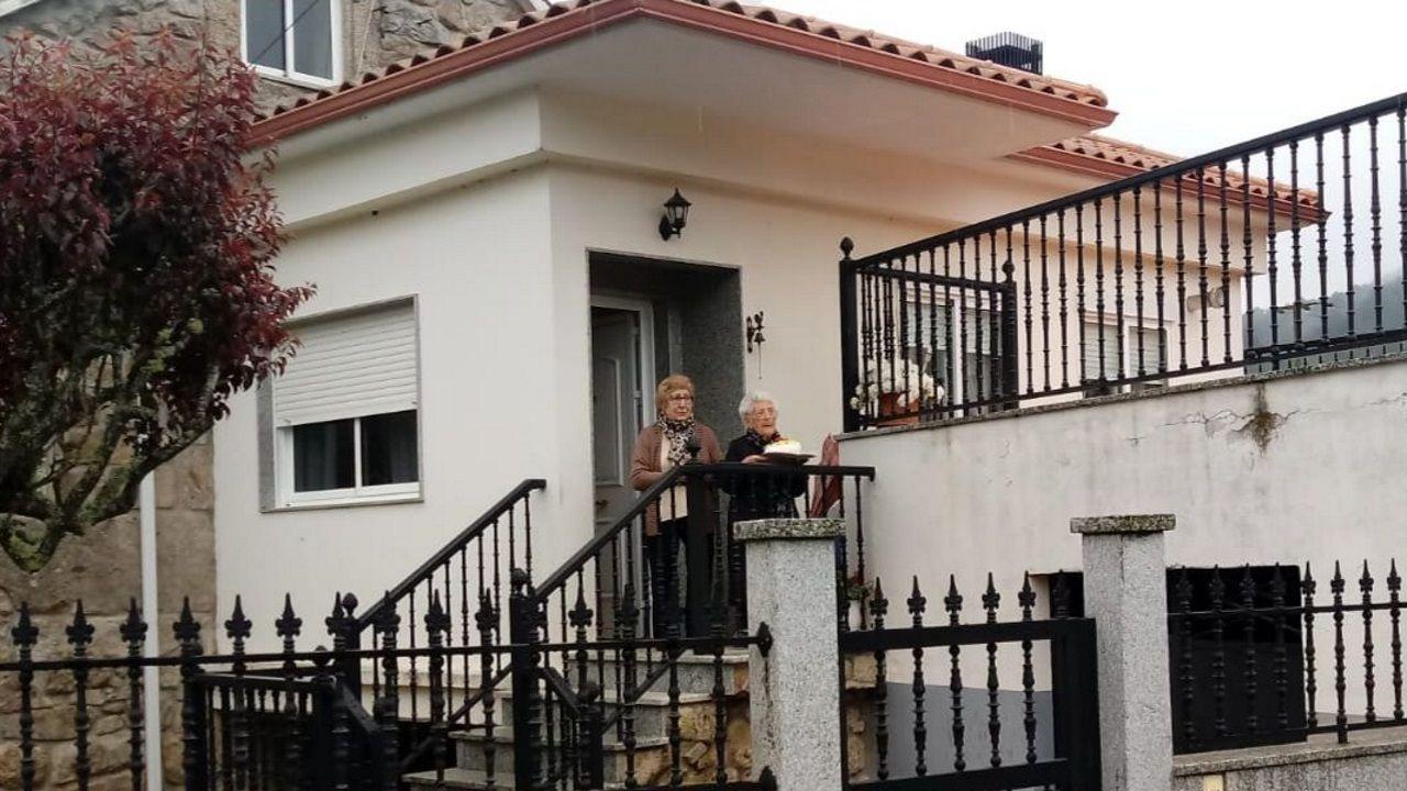 Maria, a la entrada de su casa, soplando las velas acompañada de su hija