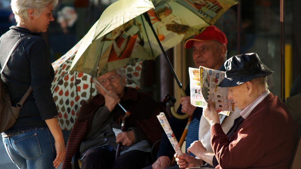 Gente mayor sentada al sol junto a un supermercado de Monforte