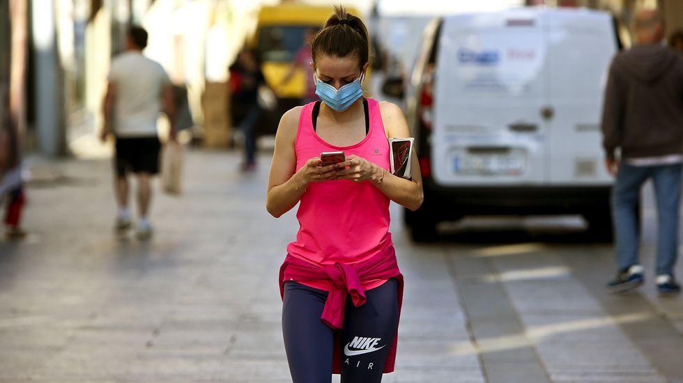 Una mujer después de practicar deporte consulta su móvil en el centro de Vigo