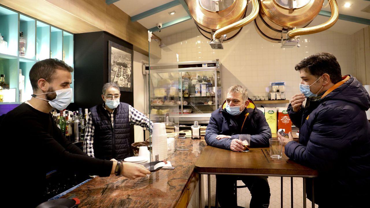 El responsable del Bar Raíces Galegas, a la izquierda, sirve a dos clientes junto a su padre