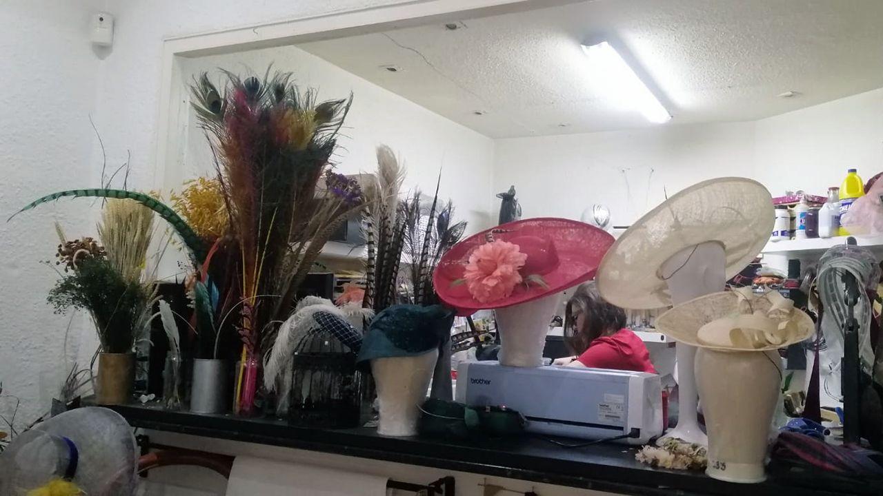 Plumas y pamelas elaboradas por Macarena, que al fondo trabaja en uno de sus diseños