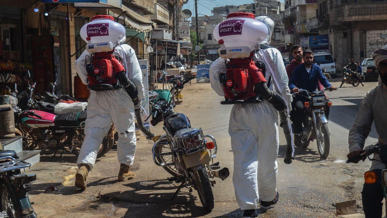 Así está el mundo en medio de la pandemia. Voluntarios durante una operación para descontaminar las calles de Idlib, al noroeste de Siria, en medio de la pandemia del coronavirus