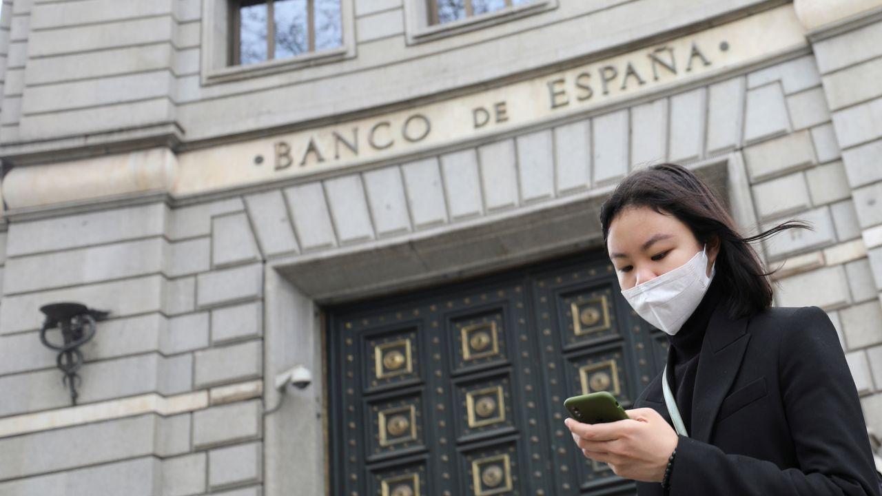 Una mujer con mascarilla frente al Banco de España en Madrid