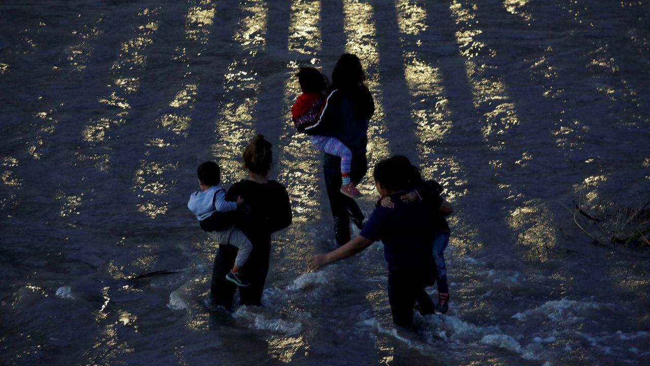 Una familia de migrantes cruza las aguas del río Bravo para alcanzar la frontera de Estados Unidos
