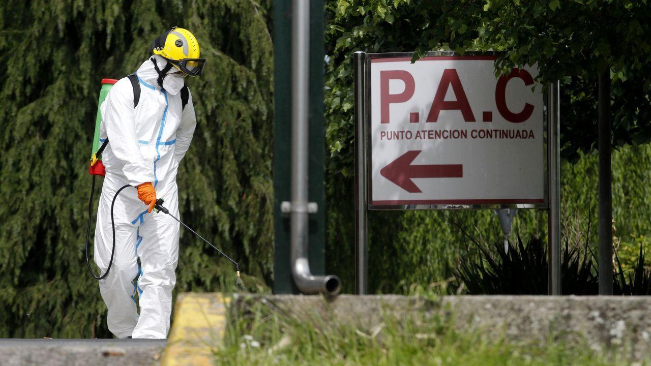 Un bombero equipado con un traje protector desinfecta esta mañana la entrada del servicio de urgencias en el hospital de Monforte
