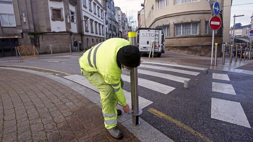 Los operarios del concello instalan bolardos para cerrar las calles por donde se ampliaran los patios pontevedreses