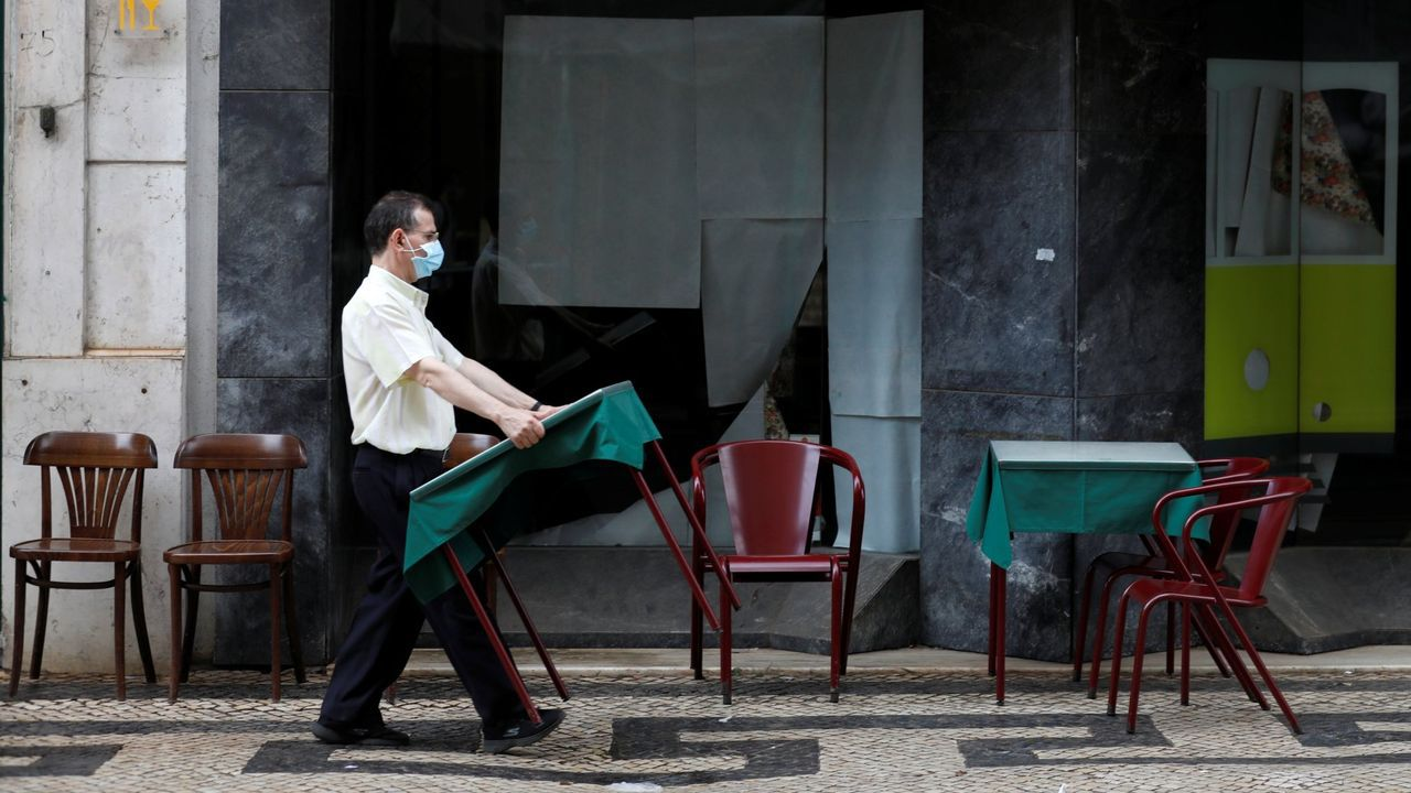 Un camarero coloca las mesas de una terraza en Lisboa