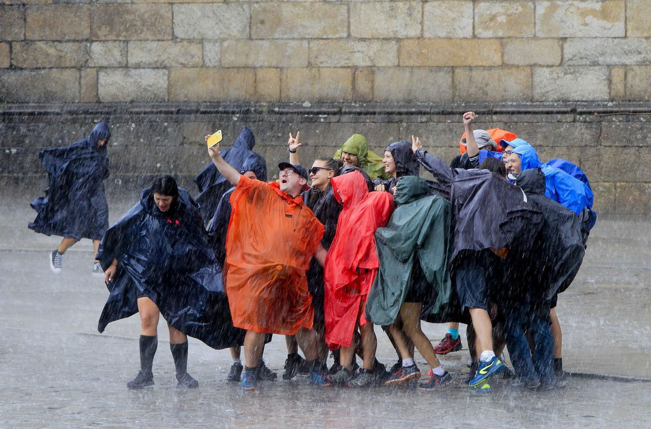 Peregrinos celebran su llegada a la Plaza del Obradoiro bajo una intensa lluvia