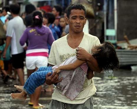 Un hombre lleva a la morgue el cuerpo sin vida de su hija en la ciudad de Tacloban.