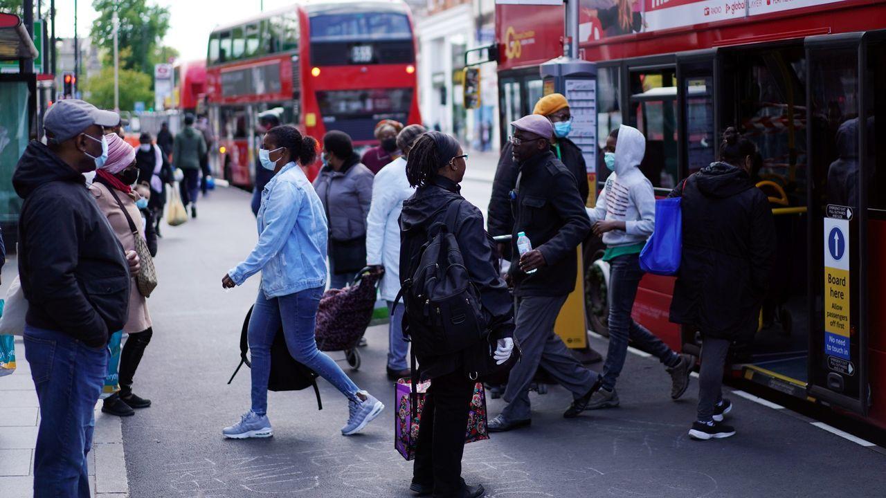 Gente sube y baja de un autobús en el distrito londinense de Brixton