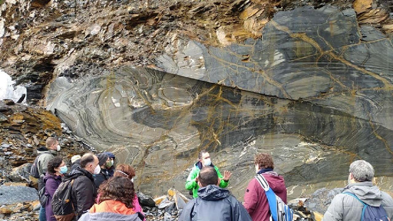 El geólogo Xosé Carlos Barros —en el centro, de verde— muestra una formación de pizarra en una visita guiada al valle de Vilarbacú que se organizó dentro del Outono Xeolóxico