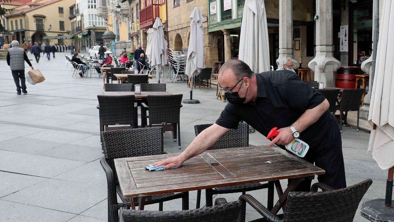 Un camarero desinfecta una mesa de una terraza del centro de Avilés