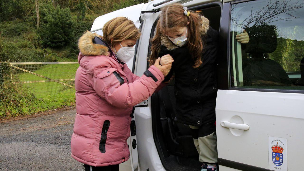 Una de las empleadas de Javier ayuda a una niña a bajar del taxi
