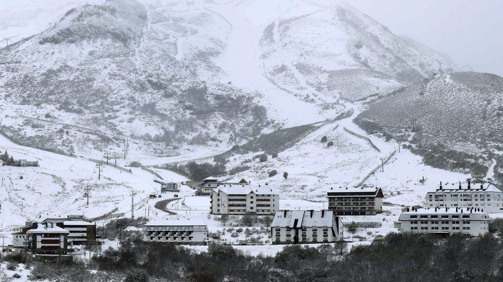 Los esquiadores disfrutan de la nieve con la estación de esquí de Valgrande-Pajares al fondo.Aspecto que presenta la estacion de esqui de Pajares