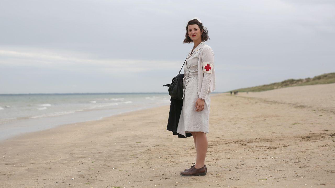 Una mujer vestida de enfermera de la época visita la histórica playa de Utah, en la costa de Normandía
