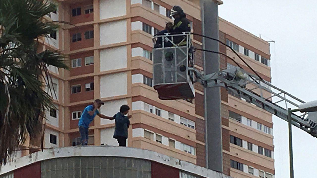 El hombre y la mujer, en la azotea del edificio, mientras los bomberos tratan de acerlos entrar en razón