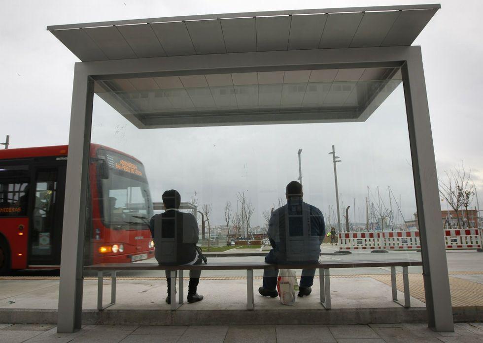 Dos vecinos aguardando el bus en la nueva marquesina instalada en la Marina.
