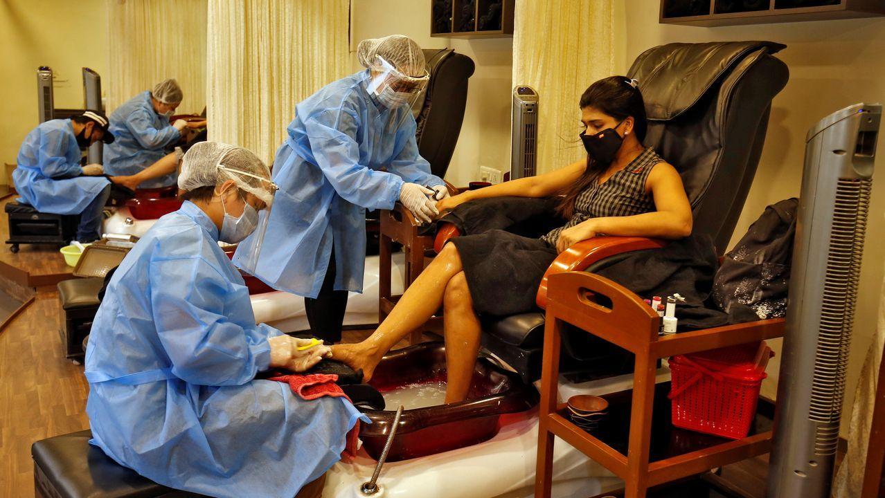 Esteticistas de un salón en India utilizan trajes de protección para atender a sus clientas