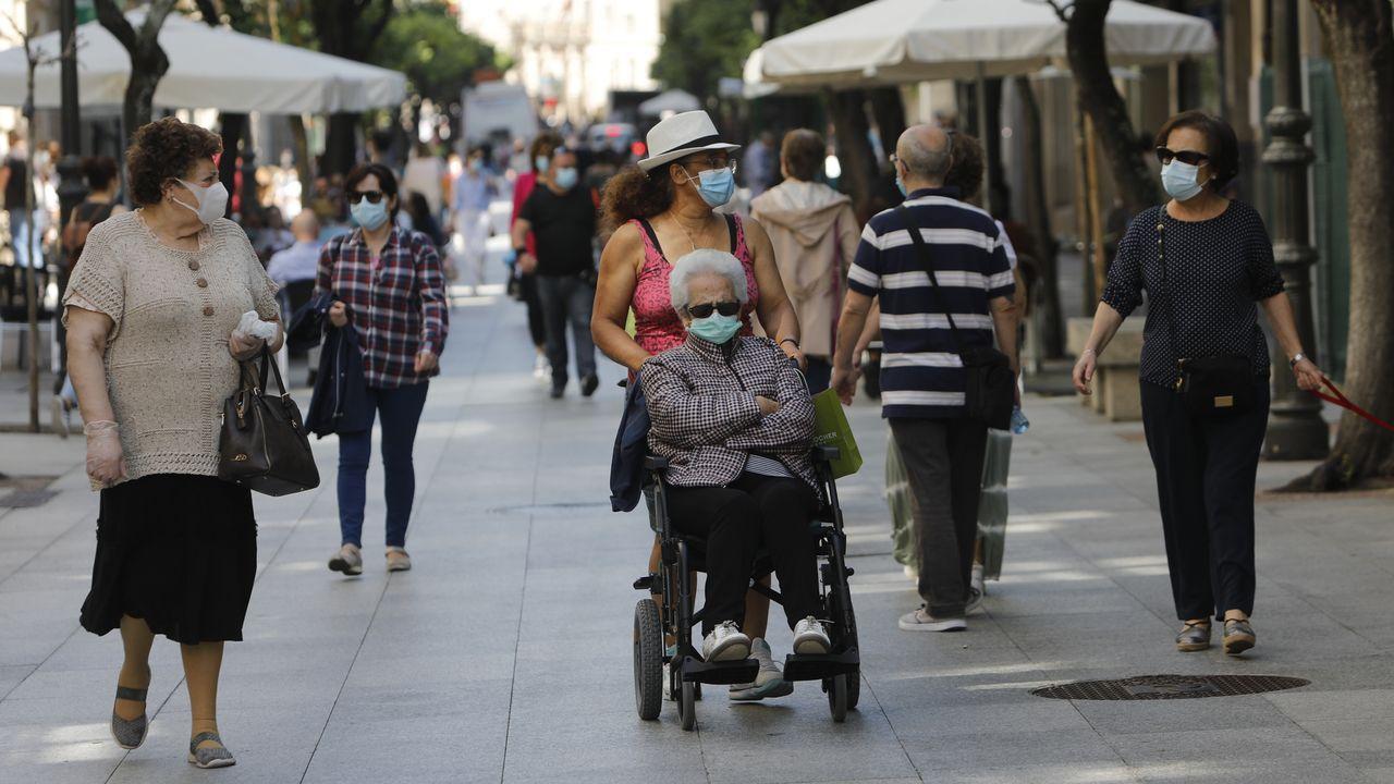 Así fue el primer día de Ourense con mascarillas obligatorias.Un matrimonio protegido con mascarillas pasea por el Campillín, en Oviedo