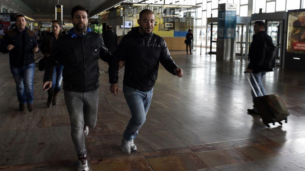 Un policía escolta los familiares de los pasajeros del vuelo siniestrado en los Alpes franceses, en el aeropuerto del Prat de Barcelona.