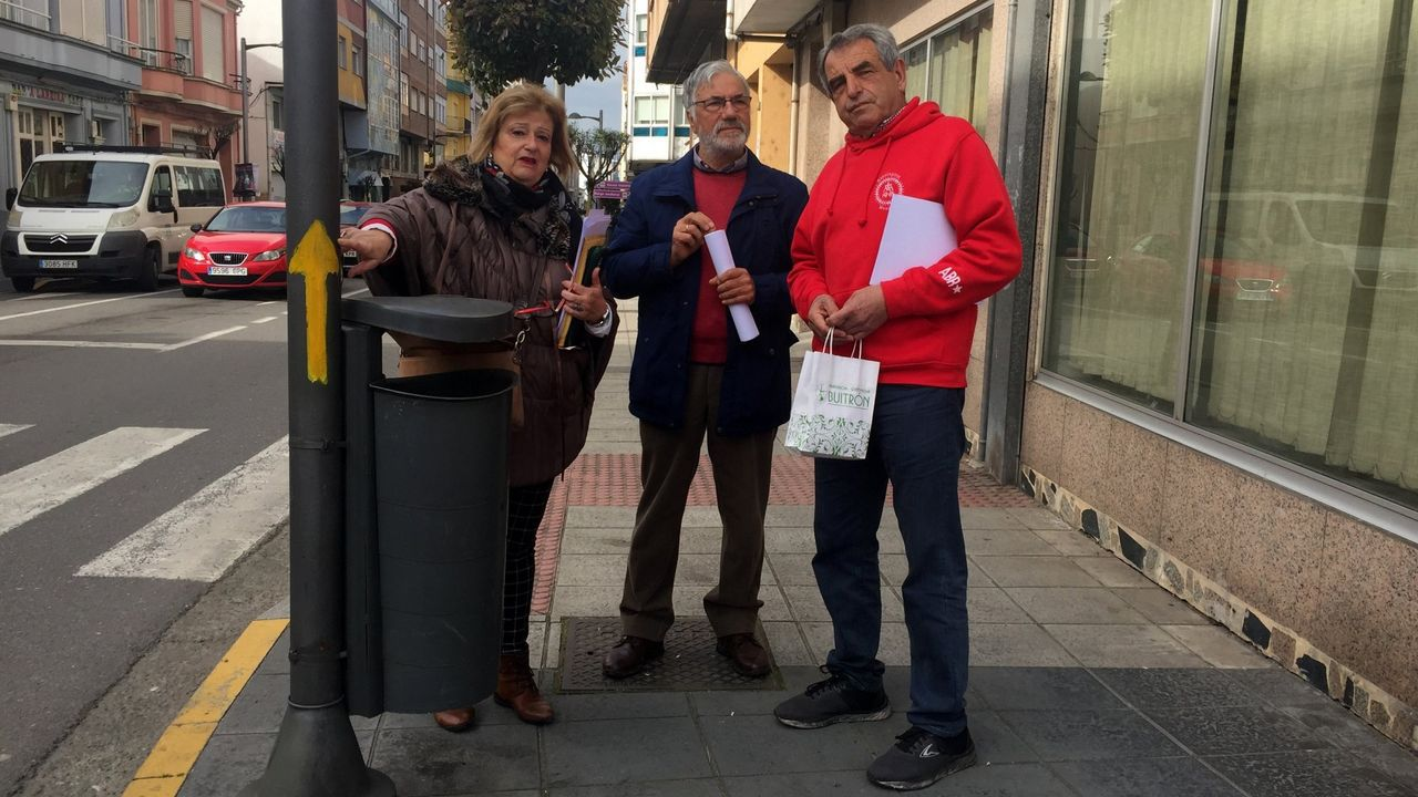 Aida Menéndez, Francisco Rodríguez y Manuel Eiriz, miembros de la directiva de la asociación, junto a una de las flechas amarillas que pintaron en el casco urbano y que han motivado la sanción