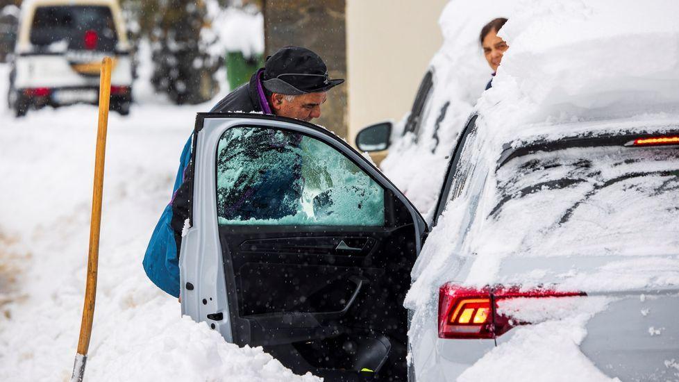 Un hombre despeja la nieve para poder acceder a su vehículo en el pueblo de Pajares (Asturias), que se encuentra en nivel rojo, lo cual implica la prohibición de circulación de vehículos articulados, camiones y autobuses.