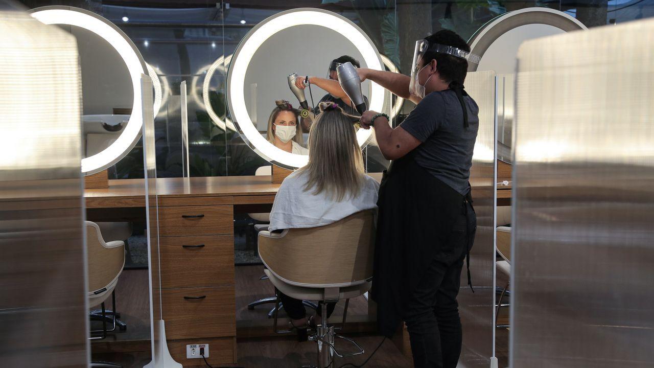 Una peluquera atiende a una cliente en medio de mamparas en Sao Paulo, Brasil